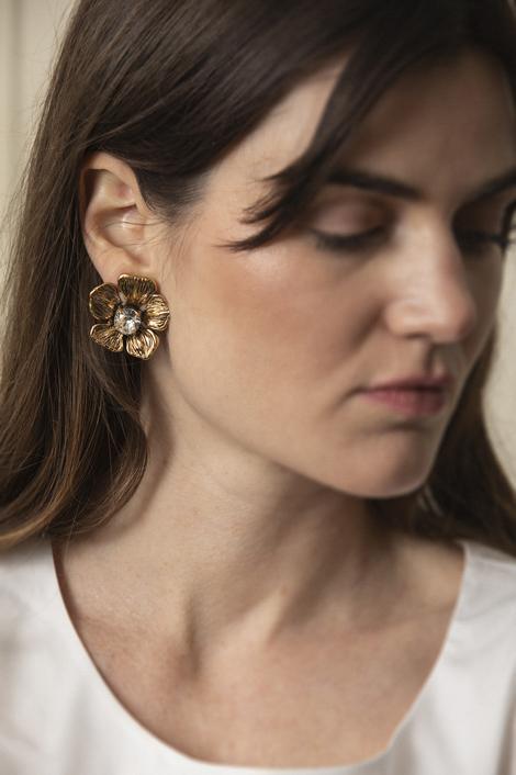 mannequin portant une paire de boucle d'oreille en fleur